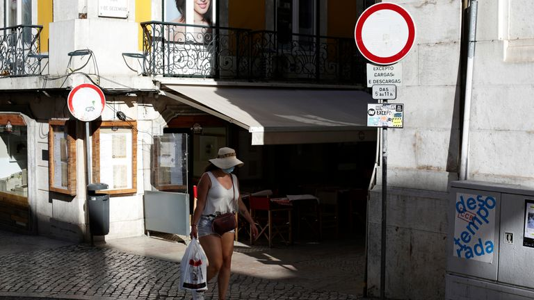 A woman wearing a face mask walks in downtown Lisbon, Thursday, July 1, 2021. Portugal's government says that from Friday it is imposing an 11 p.m. curfew in parts of the country that are seeing a surge in new COVID-19 cases including Lisbon. (AP Photo/Armando Franca)