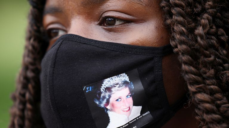A woman wears a face mask with a picture of Britain's Princess Diana, outside Kensington Palace in London, Britain, June 30, 2021. REUTERS/Henry Nicholls