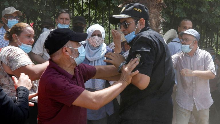 A supporter of Tunisia's biggest political party, the moderate Islamist Ennahda, scuffles with a police officer near the parliament building in Tunis, Tunisia July 26, 2021. REUTERS/Zoubeir Souissi