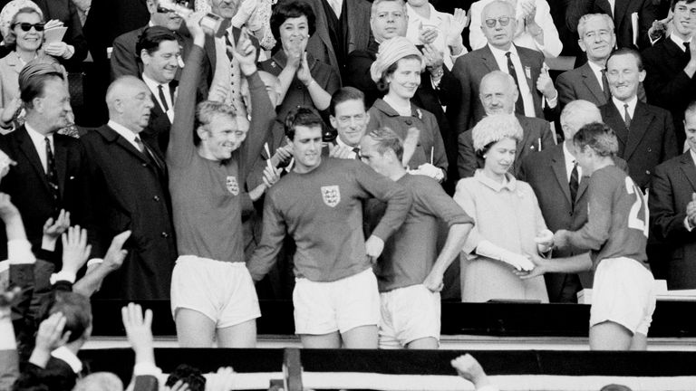 England's 1966 World Cup heroes celebrate with the trophy after it was presented to them by the Queen