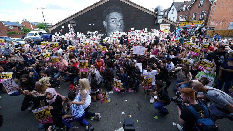 People take the knee near the Marcus Rashford mural. Pic: Ap