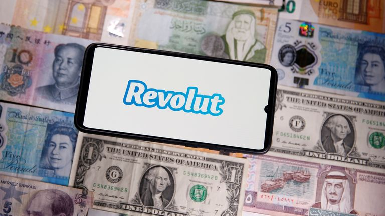 A smartphone displays a Revolut logo on top of banknotes