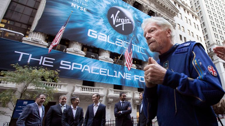 FILE - In this Monday, Oct. 28, 2019 file photo, Richard Branson, right, founder of Virgin Galactic, and company executives gather for photos outside the New York Stock Exchange before his company's IPO. Branson announced Thursday, July 1, 2021 he plans to fly into space this month on the next test flight of his Virgin Galactic rocket ship. The launch window will open July 11. (AP Photo/Richard Drew, File)