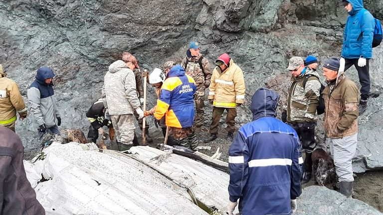 This photo released by the Russia Emergency Situations Ministry press service on Wednesday, July 7, 2021, shows Emergency Situations Ministry workers at the wreckage of a missing Antonov An-26 missing plane found near its destination airport outside the town of Palana, in Russia's Far East. Authorities in Russia say rescuers have found the bodies of nine victims a day after a plane crash in a remote area in the country's Far East. (Russia Emergency Situations Ministry press service via AP)