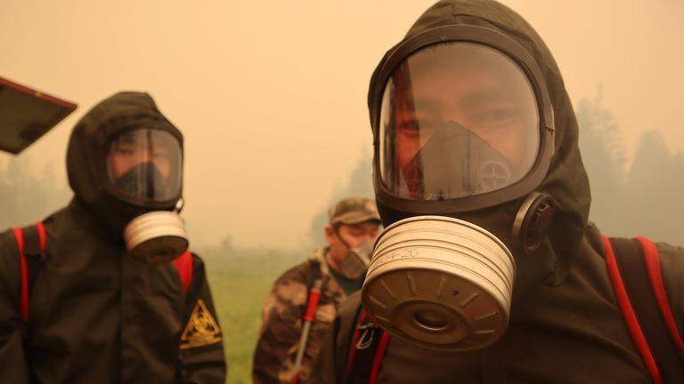Firefighters wear gas masks to protect themselves from the fire's toxic fumes