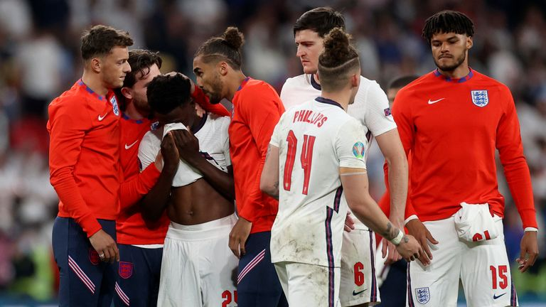 England players comfort teammate Bukayo Saka after he failed to score a penalty. Pic: AP