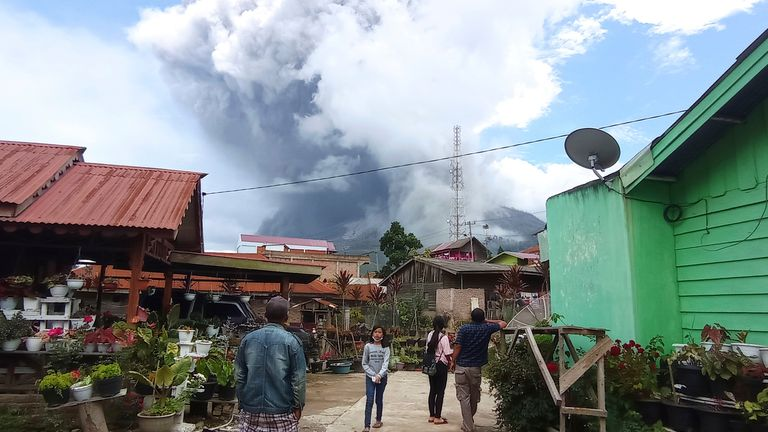 """People watch as Mount Sinabung spews volcanic materials during an eruption in Karo, North Sumatra, Indonesia. Wednesday, July 28, 2021. Sinabung is among more than 120 active volcanoes in Indonesia, which is prone to seismic upheaval due to its location on the Pacific """"Ring of Fire,"""" an arc of volcanoes and fault lines encircling the Pacific Basin.(AP Photo/Sastrawan Ginting)"""