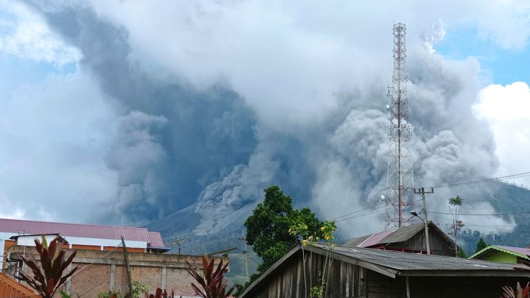 """Mount Sinabung releases volcanic materials during an eruption as seen from a school yard in Karo, North Sumatra, Indonesia, Wednesday, July 28, 2021. Sinabung is among more than 120 active volcanoes in Indonesia, which is prone to seismic upheaval due to its location on the Pacific """"Ring of Fire,"""" an arc of volcanoes and fault lines encircling the Pacific Basin.(AP Photo/Sastrawan Ginting)"""