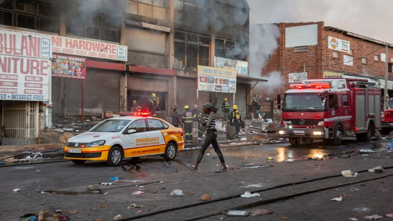 A woman walks past a fire engine as it extinguishes flames in a looted store in Alexandra township, Johannesburg. Pic: AP