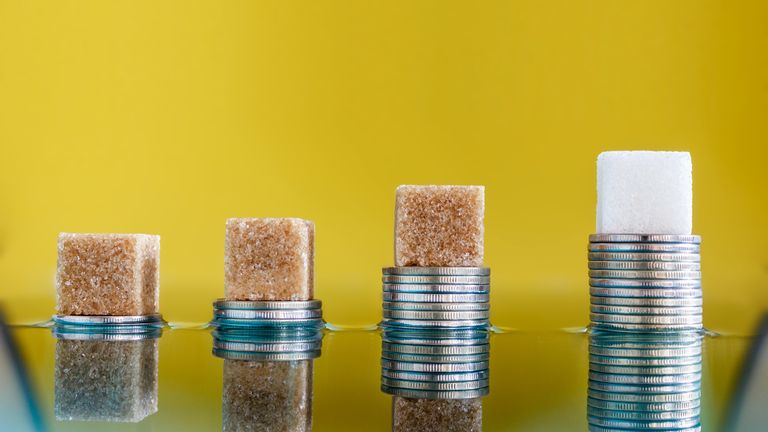 Sugar cubes on coins. Sugar price and investments