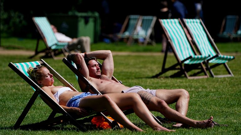 Sunbathers lounge on deck chairs in Green Park, London. Picture date: Saturday July 17, 2021.