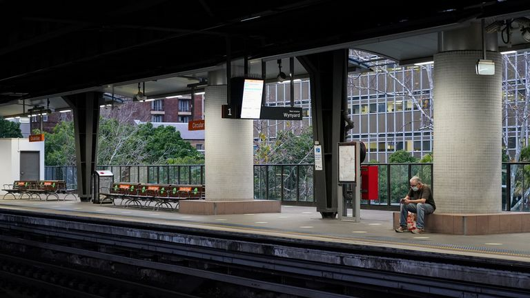 A lone passenger in protective face mask waits at the quiet Circular Quay train station during a lockdown to curb the spread of a coronavirus disease (COVID-19) outbreak in Sydney, Australia, July 28, 2021. REUTERS/Loren Elliott