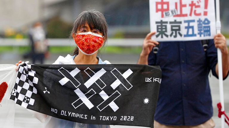 Protesters protest outside the torch-bearing ceremony in Tokyo on Friday. Pic: AP