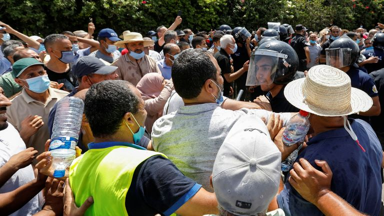 A police officer pushes back supporters of Tunisia's Ennahdha political party