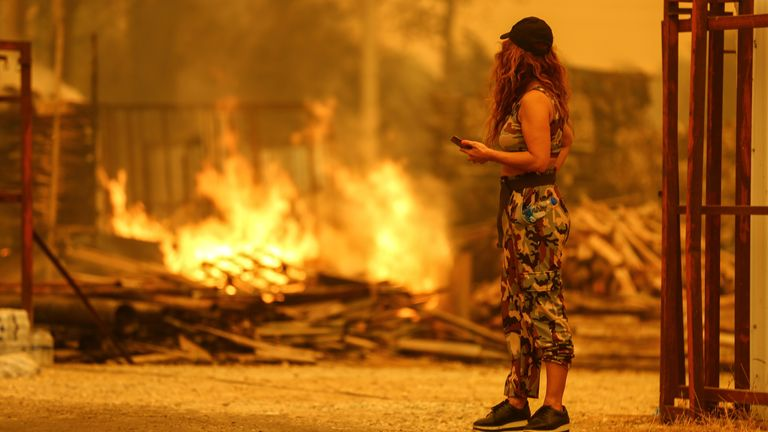 A resident watches the flames in an area scorched by a forest fire near the town of Manavgat, east of the resort city of Antalya, Turkey, July 29, 2021. REUTERS/Kaan Soyturk