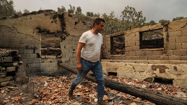A resident walks in the remains of a burnt house in an area scorched by a forest fire near the town of Manavgat, east of the resort city of Antalya, Turkey, July 29, 2021. REUTERS/Kaan Soyturk