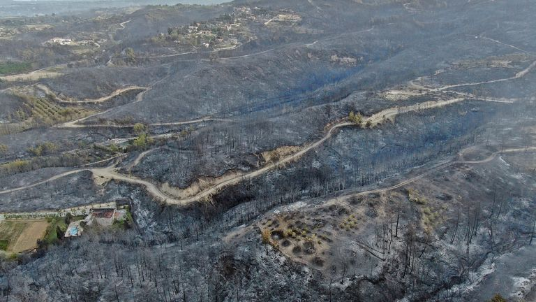 (Suat Metin/IHA via AP) An aerial photo shows destroyed houses in a village as wildfire continue to rage the forests near the Mediterranean coastal town of Manavgat, Antalya, Turkey, Thursday, July 29, 2021. Authorities evacuated homes in southern Turkey as a wildfire fanned by strong winds raged through a forest area near the Mediterranean coastal town of Manavgat. District governor Mustafa Yigit said reside