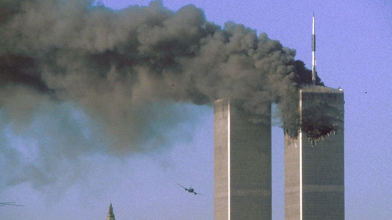 Hijacked United Airlines Flight 175 (L) flies toward the World Trade Center twin towers shortly before slamming into the south tower (L) as the north tower burns following an earlier attack by a hijacked airliner in New York City September 11, 2001. The stunning aerial assaults on the huge commercial complex where more than 40,000 people worked on an ordinary day were part of a coordinated attack aimed at the nation's financial heart. They destroyed one of America's most dramatic symbols of powe