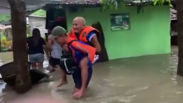 Rescuers attempted to move people from flooded and damaged properties in the Phillipines after monsoon rainfall.