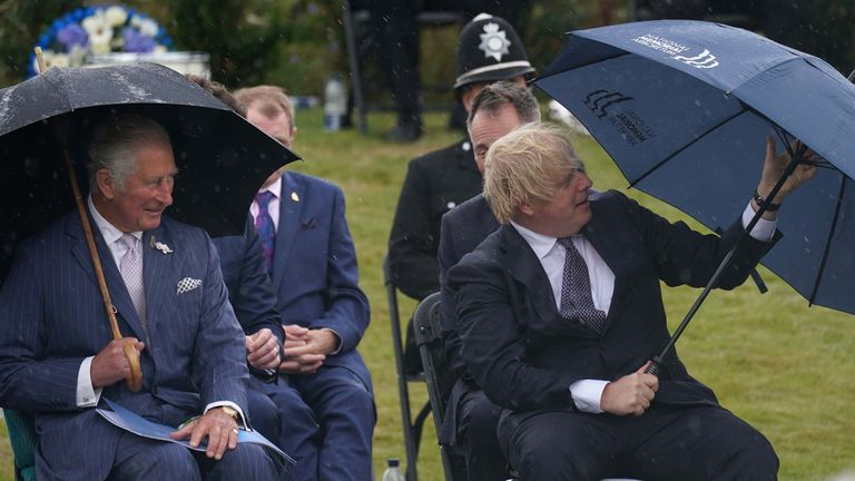 Prince Charles and Boris Johnson under umbrellas at the unveiling