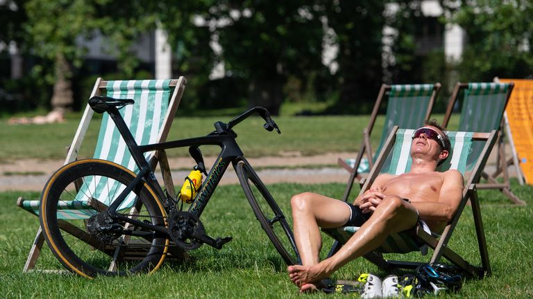 A man sunbathes in Green Park, central London
