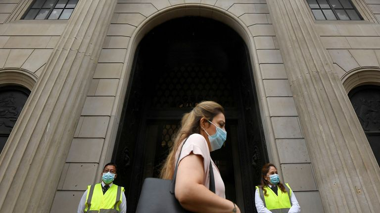 A worker wearing a protective face mask walks past the Bank of England in the City of London