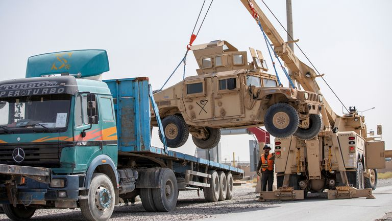 U.S. Army soldiers and contractors load High Mobility Multi-purposed Wheeled Vehicles, HUMVs, to be sent for transport as U.S. forces prepare for withdrawal
