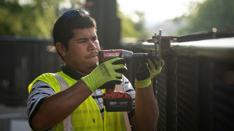 A worker is seen removing bolts from the fence with a drill