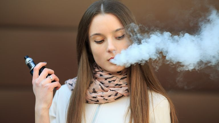 Vape teenager. Young pretty white girl in casual clothing smoking an electronic cigarette opposite modern brown background on the street in the spring. Bad habit. Vaping activity. Close up.