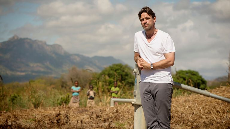 WaterAid Ambassador Dougray Scott stands by the village water pump in M'Mele Village, Cuamba District, Niassa Province, Mozambique in May 2017. Pic: WaterAid/ Eliza Powell