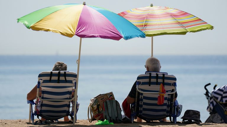 People sit under umbrallas as they enjoy the hot weather at Bournemouth Beach in Dorset