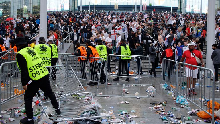 Stewards replace barricades after they were knocked over by supporters outside Wembley Stadium in London, Sunday, July 11, 2021, during the Euro 2020 soccer championship final match between England and Italy. (AP Photo/David Cliff)