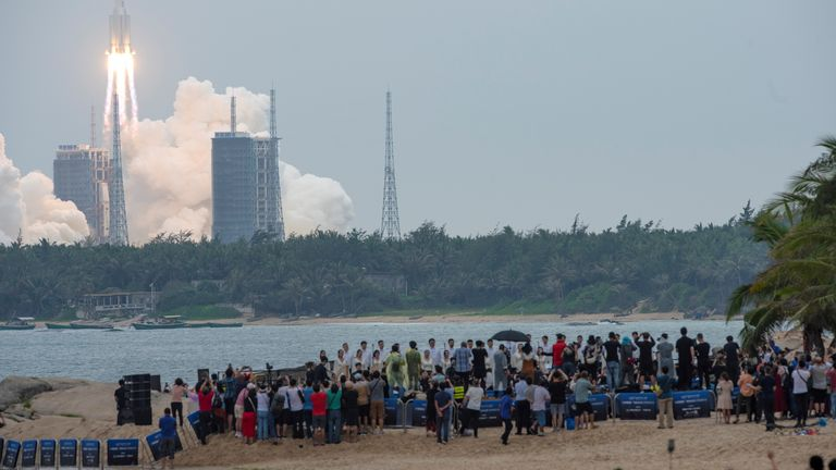 People watch from a beach as the Long March-5B Y2 rocket, carrying the core module of China's space station Tianhe, takes off from Wenchang Space Launch Center in Hainan province, China April 29, 2021