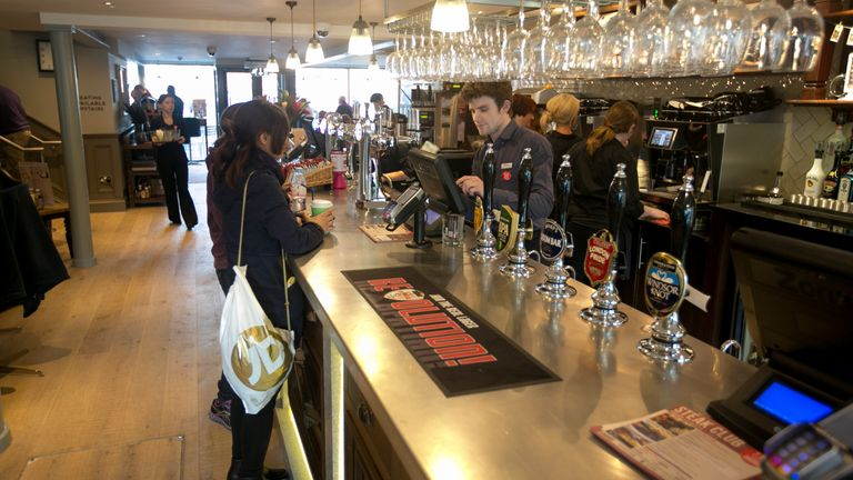 A woman orders at the bar in a Wetherspoon pub