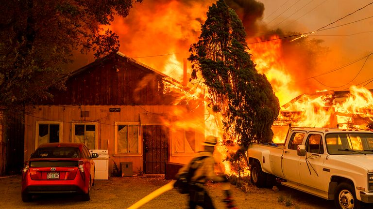 A blaze consumes a home as the Sugar Fire, part of the Beckwourth Complex Fire, rages in California