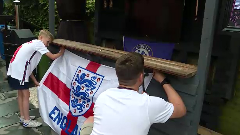 England fans Liam and Nolan hang up a flag ahead of the semi-final against Denmark