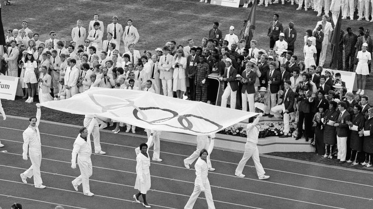 Tyus (third from left) helps to carry the Olympic flag in Los Angeles during the 1984 opening ceremony.