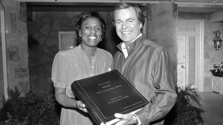 On behalf of the U.S. Olympic Committee Tyus accepts a memorial autograph book from actor Robert Wagner signed by more than 100 stars who were on a TV special in 1984