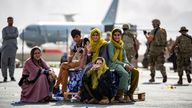 Children wait for the next flight out of Hamid Karzai International Airport in Kabul on Thursday after being told they are on the list to depart