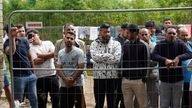 FILE PHOTO: Migrants gather near a fence at a temporary detention center in Kazitiskis, Lithuania, August 12, 2021. Picture taken on August 12, 2021. REUTERS/Janis Laizans/File Photo