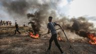 Protesters burn tyres after clashes with Israeli security forces at the border fence with Israel. Pic AP
