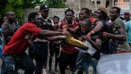 People fight over an envelope with a cash donation left by an employee of former President Michel Martelly in Les Cayes