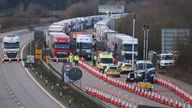 Police vehicles, barriers and road cones mark the front of the line of freight lorries in Operation Brock on the M20 near Ashford in Kent