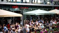 People sit at an outdoor restaurant on the South Bank in London
