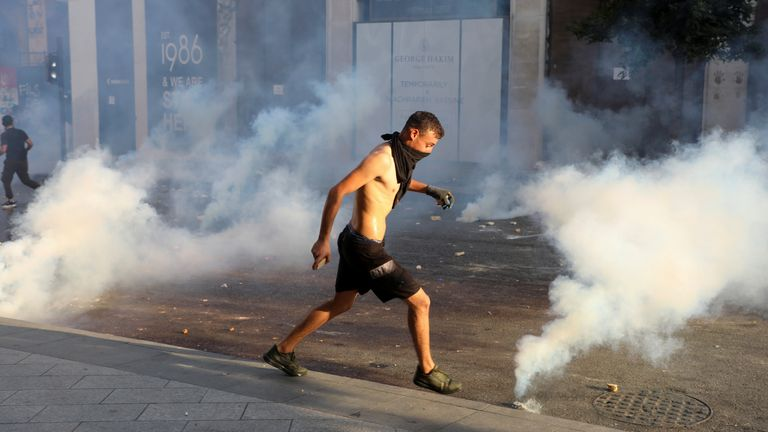 A demonstrator runs amid smoke rising from tear gas during a protest near parliament, as Lebanon marks the one-year anniversary of the explosion in Beirut, Lebanon August 4, 2021. REUTERS/Mohamed Azakir