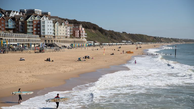 Two surfers make their way into the sea off of Boscombe beach in Dorset. Picture date: Friday April 2, 2021.