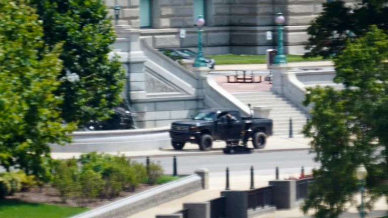 A robot is seen next to a person in a pickup truck parked on the sidewalk in front of the Library of Congress' Thomas Jefferson Building, as seen from a window of the U.S. Capitol, Thursday, Aug. 19, 2021, in Washington. A man sitting in the pickup truck outside the Library of Congress has told police that he has a bomb, and that's led to a massive law enforcement response to determine whether it's an operable explosive device. (AP Photo/Alex Brandon)