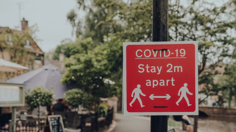 Red Covid-19 Stay 2 Metres Apart sign on a sidewalk in Bourton-on-Water, Cotswolds, UK, during COVID 19 pandemic. Selective focus.