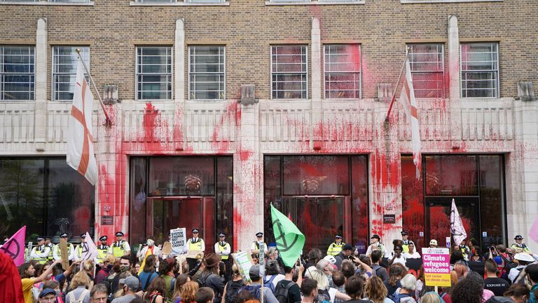 Police officers stand in front of one of the buildings of the Guildhall, which has been daubed in paint, as an Extinction Rebellion protest makes its way through the City of London. Picture date: Friday August 27, 2021.