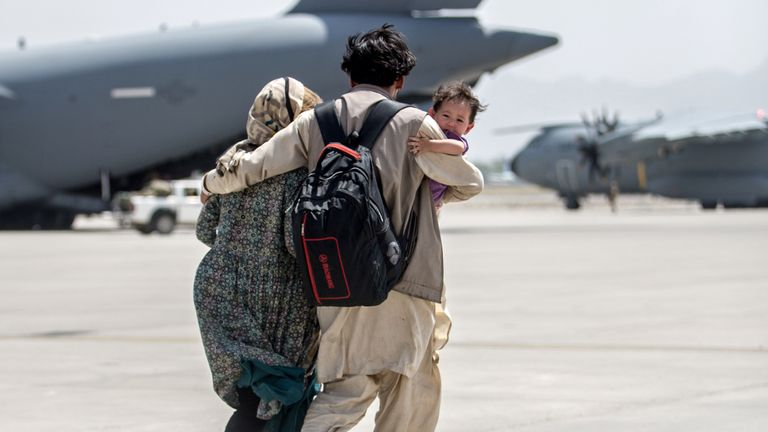 A family walks towards a U.S. Air Force Boeing C-17 Globemaster III during an evacuation at Hamid Karzai International Airport, Afghanistan, August 22, 2021. Picture taken August 22, 2021.  U.S. Marine Corps/Sgt. Samuel Ruiz/Handout via REUTERS.  THIS IMAGE HAS BEEN SUPPLIED BY A THIRD PARTY. THIS PICTURE WAS PROCESSED BY REUTERS TO ENHANCE QUALITY. AN UNPROCESSED VERSION HAS BEEN PROVIDED SEPARATELY.